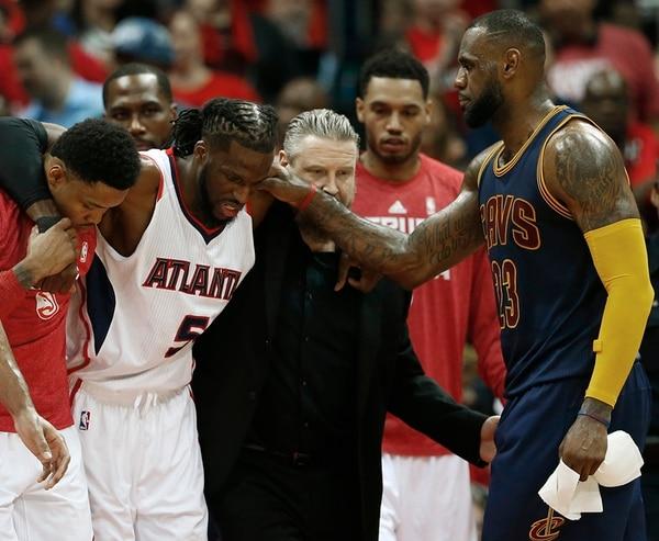 LeBron James condolece a DeMarre Carroll en su salida del partido por una lesión en la pierna. | AP