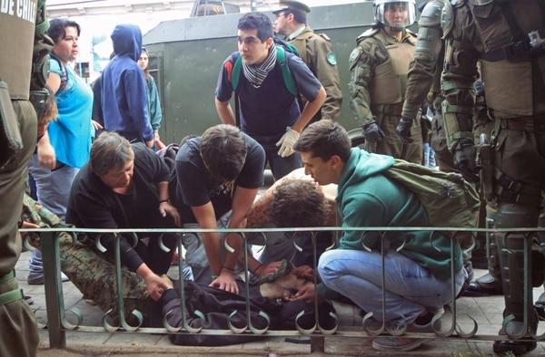 Fotografía cedida de manifestantes que ayudan a uno de los dos jóvenes baleados