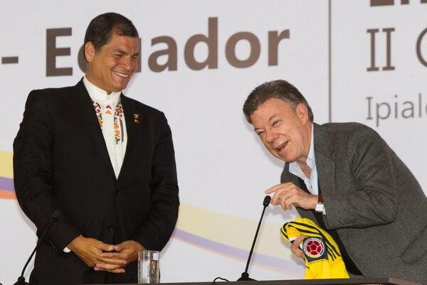 El presidente de Colombia, Juan Manuel Santos (derecha), habla junto a su homólogo de Ecuador, Rafael Correa (izquierda), después de intercambiar camisetas de las selecciones de fútbol de cada país, al concluir la reunión del II Gabinete Binacional en la zona de frontera.