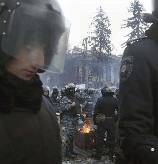 Policías antidisturbios toman un descanso en Kiev. | AFP