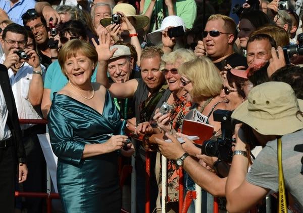 La canciller alemana, Ángela Merkel, en una firma de autógrafos a su llegada a una función de ópera en Bayreuth, Alemania, en julio del 2012. Merkel figura como favorita en las elecciones del próximo domingo. | AFP.