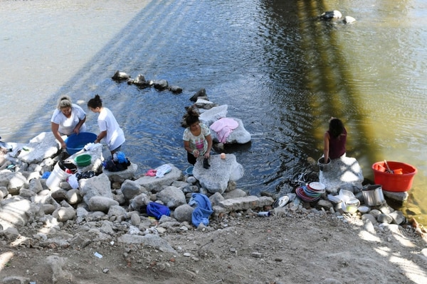 Mujeres lavan ropa y trastos de cocina en las contaminadas aguas del río Lempa en Citala, 100 kilómetros al norte de San Salvador.