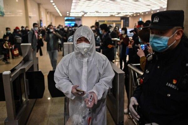 Un hombre vestido con un traje protector llega a la estación de tren de Hankou, en Wuhan, para abordar uno de los primeros trenes que salen de la ciudad en la provincia central de Hubei, en China, el 8 de abril del 2020. Foto: AFP