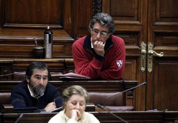 El diputado oficialista Darío Pérez (der.) escuchó ayer la intervención de sus colegas, durante la sesión de la Cámara de Representes en Montevideo (Uruguay) sobre el proyecto de ley que contempla legalizar el cultivo, distribución y venta de marihuana.