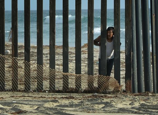 Un hombre miraba ayer hacia los Estados Unidos desde el lado mexicano tras la valla fronteriza en San Diego. | AFP