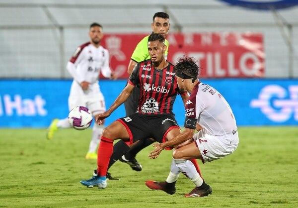 Alex López pelea la pelota con el volante morado, Christian Bolaños. Fotografía: John Durán.