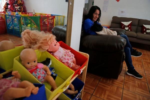 Eugenia de Buccilli, voluntaria del hogar, carga a una niña con hidranencefalia en las instalaciones del albergue.