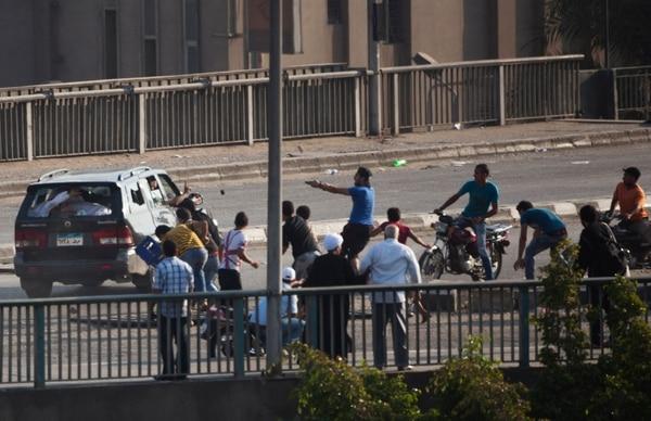 Un partidario del depuesto presidente egipcio (de azul), encañona a un conductor en las calles de El Cairo. Las protestas se han extendido todo el día en Egipto. AP