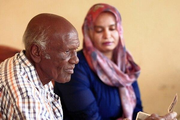 Amin Israil, nieto de un judío iraquí que se estableció en Sudán y cuya familia se convirtió más tarde al Islam, y su hija Salma ven viejas fotografías familiares juntos durante una entrevista con AFP en su casa en Wad Madani, la capital del centro-este de Sudán. -Estado de Jazirah, el 11 de febrero de 2021. - La comunidad judía en Sudán era una de las más pequeñas de Medio Oriente, pero, como las de otros estados árabes, disminuyó en la segunda mitad del siglo XX, a medida que las tensiones en torno a la La creación de Israel en 1948 impregnó la región. Como en otras partes del mundo árabe, los judíos sudaneses soportaron la peor parte del creciente sentimiento antiisraelí en medio del conflicto con el estado judío. Décadas más tarde, sus descendientes ven un acercamiento reciente entre su país e Israel como una oportunidad para conectarse con sus orígenes. . (Photo by Ebrahim HAMID / AFP)