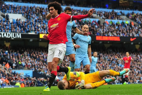 El arquero Joe Hart impide una acción de peligro de Marouane Fellaini en el derbi de Manchester.