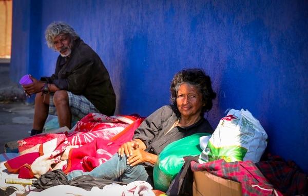 Rafael Ángel Lagos y Xinia María Castillo duermen todas las noches a orillas de la calle en barrio Cristo Rey, San José, con tan solo unas prendas para cubrirse del frío, unas cobijas y una sombrilla. Foto: Alonso Tenorio