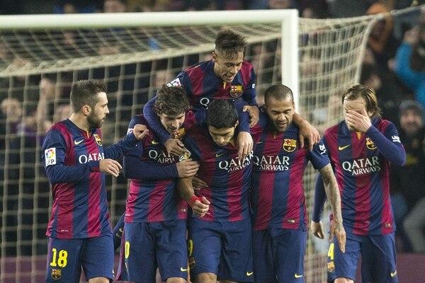 El delantero uruguayo del Barcelona, Luis Suárez (centro), es felicitado por sus compañeros tras marcar el segundo gol ante el Elche. | EFE