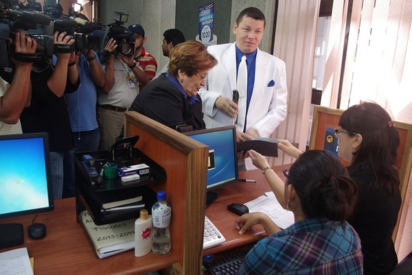 Óscar López llegó al TSE vestido con su típico traje blanco para inscribir su candidatura presidencial por el PASE. A su lado, Zulema Villalta, quien pretende una diputación con el mismo partido.   CORTESÍA DEL TSE.