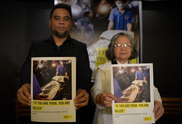 Wilnor Papa (izq.) y la hermana Maria Cordero, ambos de Amnistía Internacional, muestran copias de su informe en Manila el 1 de febrero. En el informe, Amnistía habla de posibles crímenes contra la Humanidad cometidos por la Policía de Filipinas.