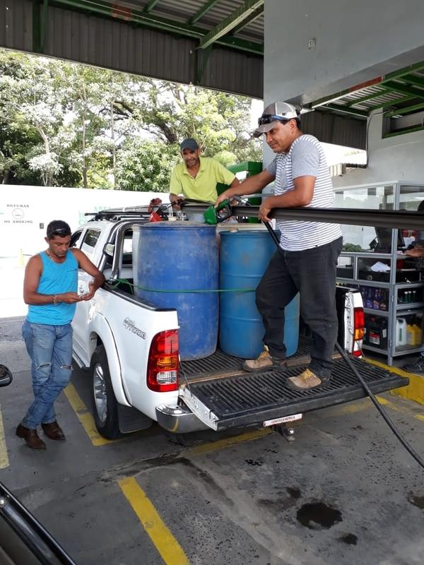 Consumidores llenan pichingas de combustible en Bagaces. Foto: Esteban Oviedo.