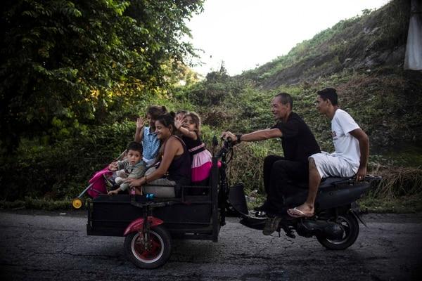 Migrantes hondureños viajan en un carrito de motocicleta improvisado en Huixtla, de camino al estado de Mapastepec, Chiapas, México. Foto: AFP