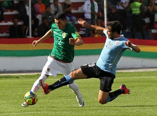 El jugador de la selección de Bolivia Juan Carlos Zampiery (izquierda) disputa el balón con con Álvaro González, de Uruguay durante el partido por las eliminatorias sudamericanas del Mundial Rusia 2018.