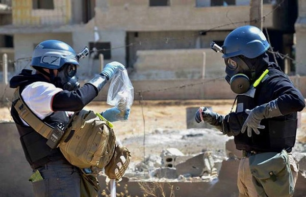 Personal de la OPAQ toma muestras de arena, cerca de donde impactó un proyectil, 28 de agosto en Ain Terma, Siria. Los investigadores indagan el posible uso de armas químicas. | AP.