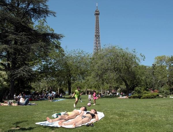 Personas toman el sol y disfrutan del espacio verde en París, Francia. La imagen corresponde a un verano del 2008.