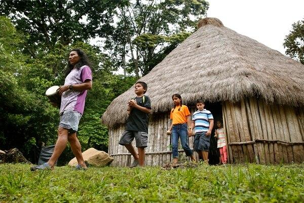 El chamán Luis Quetzal encabeza el grupo que sale de la casa cónica cabécar hacia el ritual de Temazcal. Es seguido por algunos niños que cantan y tocan los intrumentos propios del ritual. Foto: Albert Marín.