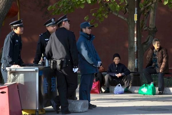 Agentes policiales chinos se mantenían expectantes ayer en un punto de control en Pekín, cerca del escenario de la reunión del Partido. | AP.