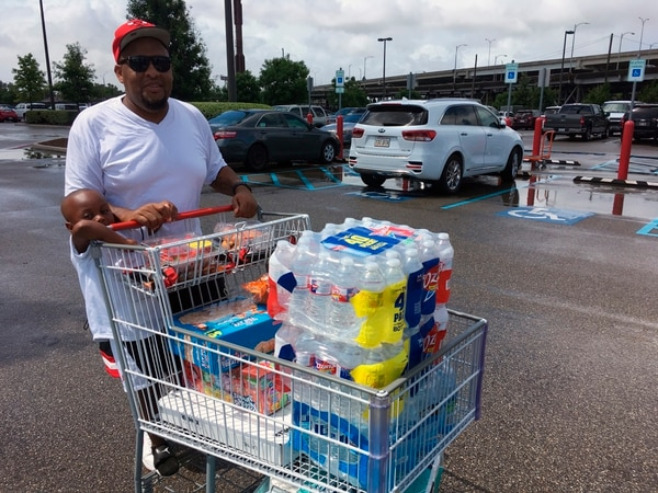 Terrence Watkins y su hijo Kang, de 3 años, compraron agua y otros suministros en Nueva Orleans, el viernes 12 de julio del 2019, ante la amenaza de la tormenta tropical Barry. Foto: AP