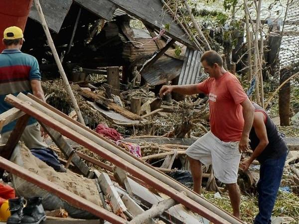 Habitantes del poblado de Antillas, en la provincia de Holguin en Cuba, a 751 km este de La Habana, buscan entre los escombros que dejó el hurarán a su paso por esta isla. | AFP