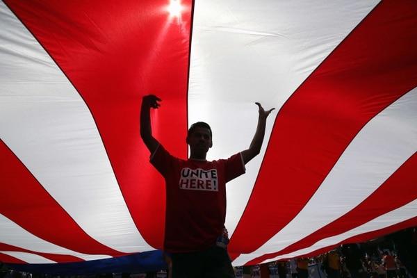 Un abogado de inmigración sostiene una bandera de Estados Unidos durante el Día Nacional de la Dignidad y el Respeto.