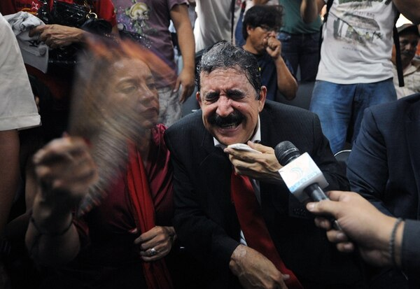 El expresidente de Honduras Manuel Zelaya recibe ayuda en las afueras del Congreso, el martes, tras ser sacado con gases lacrimógenos. | AFP