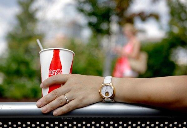 Un consumidor se sienta frente a la entrada de la atracción Mundo Coca Cola, en Atlanta.