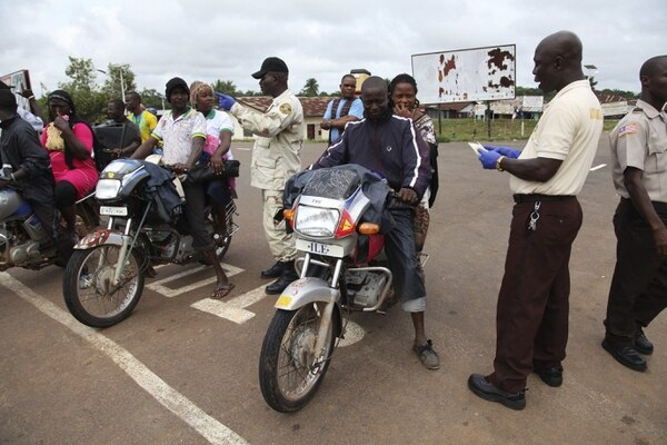 Varios oficiales liberianos de migración se protegen con guantes para evitar el contagio del ébola, mientras inspeccionan los pasaportes de varios ciudadanos de Sierra Leona en el paso fronterizo de Bo Wateside, en Liberia.