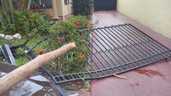 El portón principal de la casa quedó destrozado luego del violento impacto. Foto: Andrés Garita