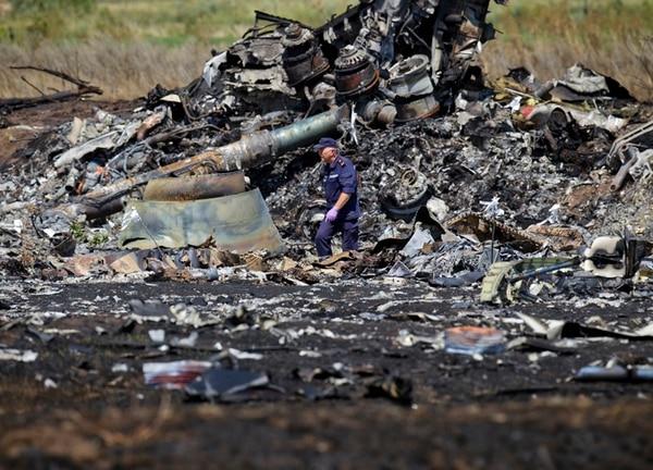 Un socorrista ucraniano camina entre los escombros carbonizados en el lugar del accidente del avión de Malaysia Airlines, en el este de Ucrania. | AP
