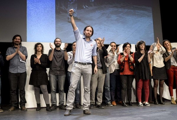 El líder del partido antiausteridad español Podemos, Pablo Iglesias (centro) saluda mientras varios correligionarios le aplauden durante una conferencia de prensa en Madrid, este miércoles 5 de mayo.