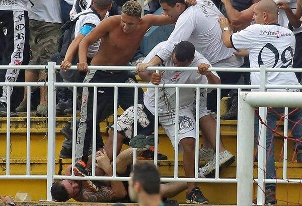 Al menos tres personas resultaron gravemente heridas en el enfrentamiento entre aficionados que interrumpió el juego entre Paranaense y Vasco. | AFP