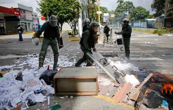 Soldados de la Guardia Nacional limpian una carretera bloqueada por manifestantes opositores en Caracas, Venezuela.