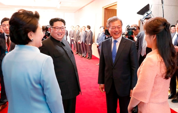 Kim Jong-un (izquierda), acompañado por su esposa, Ri Sol-ju (derecha), recibieron la bienvenida por parte de Moon Jae-in y su cónyuge, Kim Jung-sook, el viernes 27 de abril del 2018 en la aldea de Panmunjon.