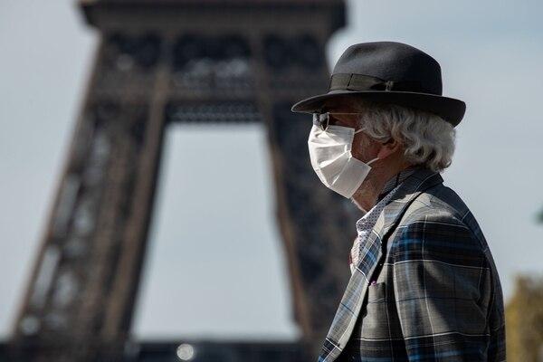 Un hombre con una mascarilla camina cerca de la torre Eiffel en París el día 22 de un encierro en Francia destinado a frenar la propagación de la pandemia causada por el nuevo coronavirus. Foto: AFP