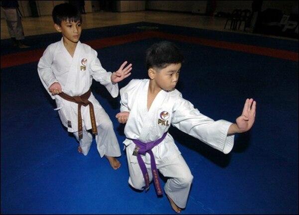 (ARCHIVO) Miguel Avenido (D) y Sham Nebrija (I) de Filipinas, practican un Kata antes de la apertura de la 13 Copa Mundial de Karate Kobe Osaka internacional (KOI), en Manila, el 14 de agosto de 2004. El venezolano Antonio Díaz logró la medalla de plata en kata individual el 14 de noviembre de 2008 en la segunda jornada del Mundial-2008 de Tokio de karate. Niños de Filipinas practican un kata   AFP