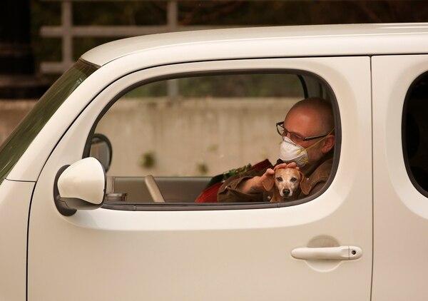 Chris Shiery acaricia a su perro Ruby, mientras espera evacuar la ciudad de Sonoma por los incendios que acechan a California.