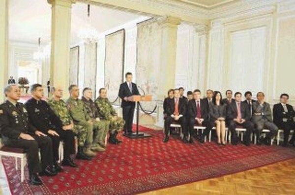 El presidente Santos, flanqueado por su gabinete y la cúpula militar, anunció ayer los detalles del proceso. | AFP.