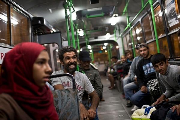 Un emigrante no oculta su felicidad luego de abordar un autobús en la estación ferroviaria de Keleti, en Budapest, para emprender viaje hacia Austria. Para muchos de ellos, sin embargo, la meta es establecerse en Alemania. | AP