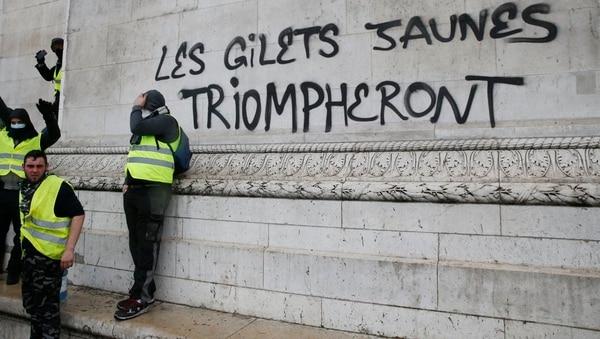 Manifestantes al lado de la pinta sobre el Arco del Tirunfo que proclama: Los chalecos amarillos triunfarán. Foto: AFP