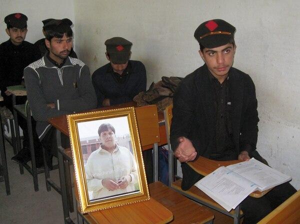 Estudiantes paquistaníes se sientan al lado de la imagen de Atizaz Hasan, joven que falleció en su intento por detener un atacante suicida que tenía como objetivo su escuela en un remoto pueblo de Hangu, Pakistán.
