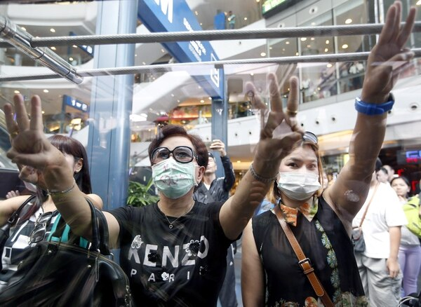Manifestantes tailandeses cierran sus bocas y parpadea el signo de 'hermandad, la libertad y la igualdad', durante una manifestación contra el golpe de estado en un centro comercial en Bangkok.