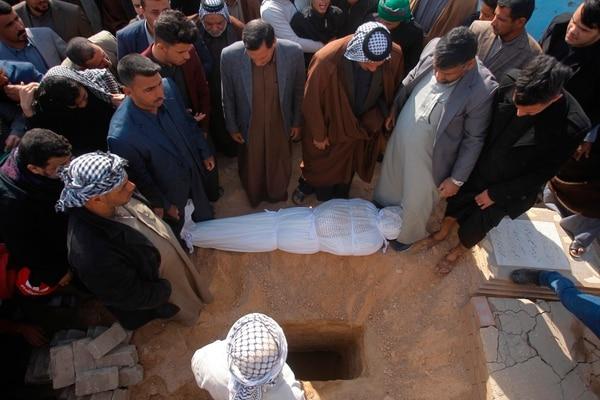 Dolientes se alistaban a sepultar un manifestante muerto durante enfrentamientos entre grupos opositores al gobierno y seguidores del clérigo chiita Moqtada Sadr en la ciudad de Najaf.