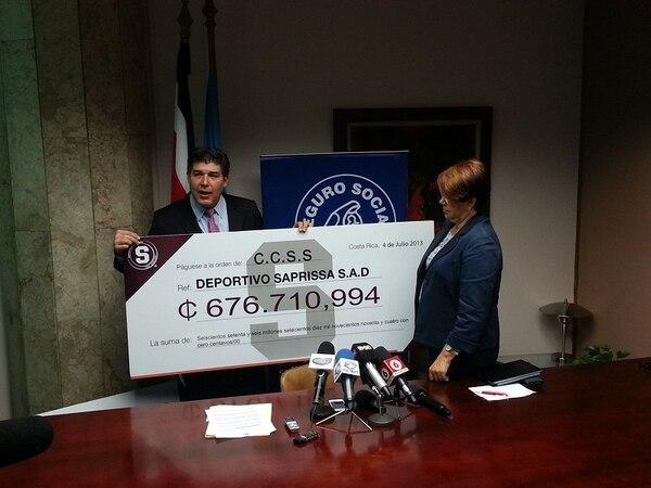 El directivo de Saprissa Marco Cercone (izquierda) , entrega un cheque simbólico a la presidenta de la Caja, Ileana Balmaceda
