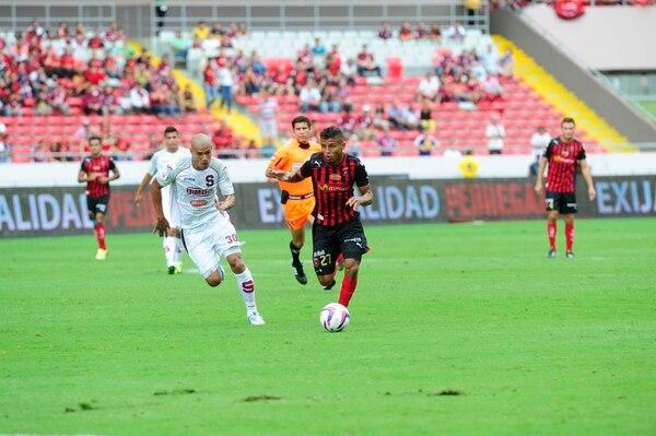 El árbitro Wálter Quesada (atrás) sigue la acción del clásico entre el morado Douglas Sequeira (izq.) y el rojinegro Johan Venegas, este domingo en el Estadio Nacional. La Liga goleó 3-0.