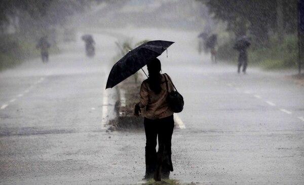 Una mujer india sostiene un paraguas mientras se dirige a un refugio cerca de Chatrapur en el distrito de Ganjam unos 200 kilómetros (125 millas) de la ciudad oriental india de Bhubaneswar, India