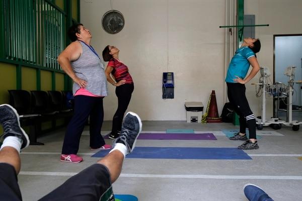 Angelina Gómez (de blusa roja) y Noylin Gómez (de gris) hacen estiramientos con Gabriela Rojas, experta en Ciencias del Movimiento Humano. Fotos: Mayela López